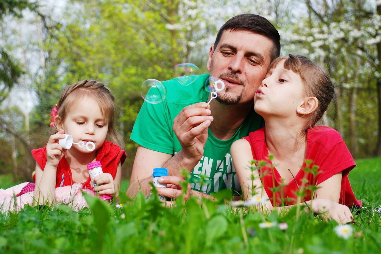 Dad engaging in healthy play with kids in summer