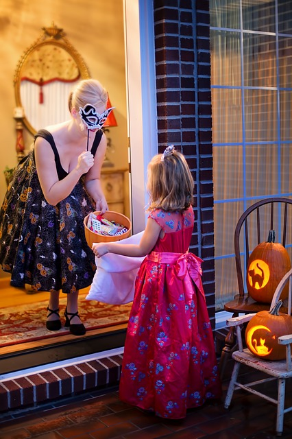 Butterfly Beginnings Counseling tips for stress-free Halloween image of woman giving tirck-or-treating child treats