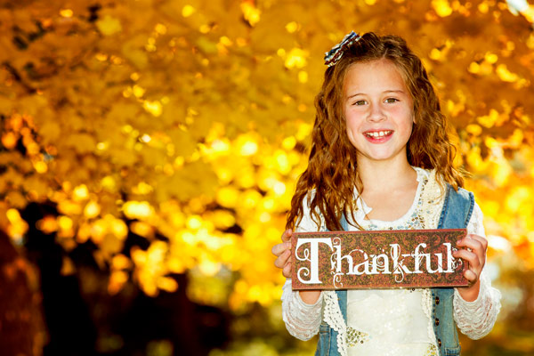 "Girl holding ""thankful"" sign to show how lay therapy can foster gratitude with Butterfly Beginnings Play Therapy"