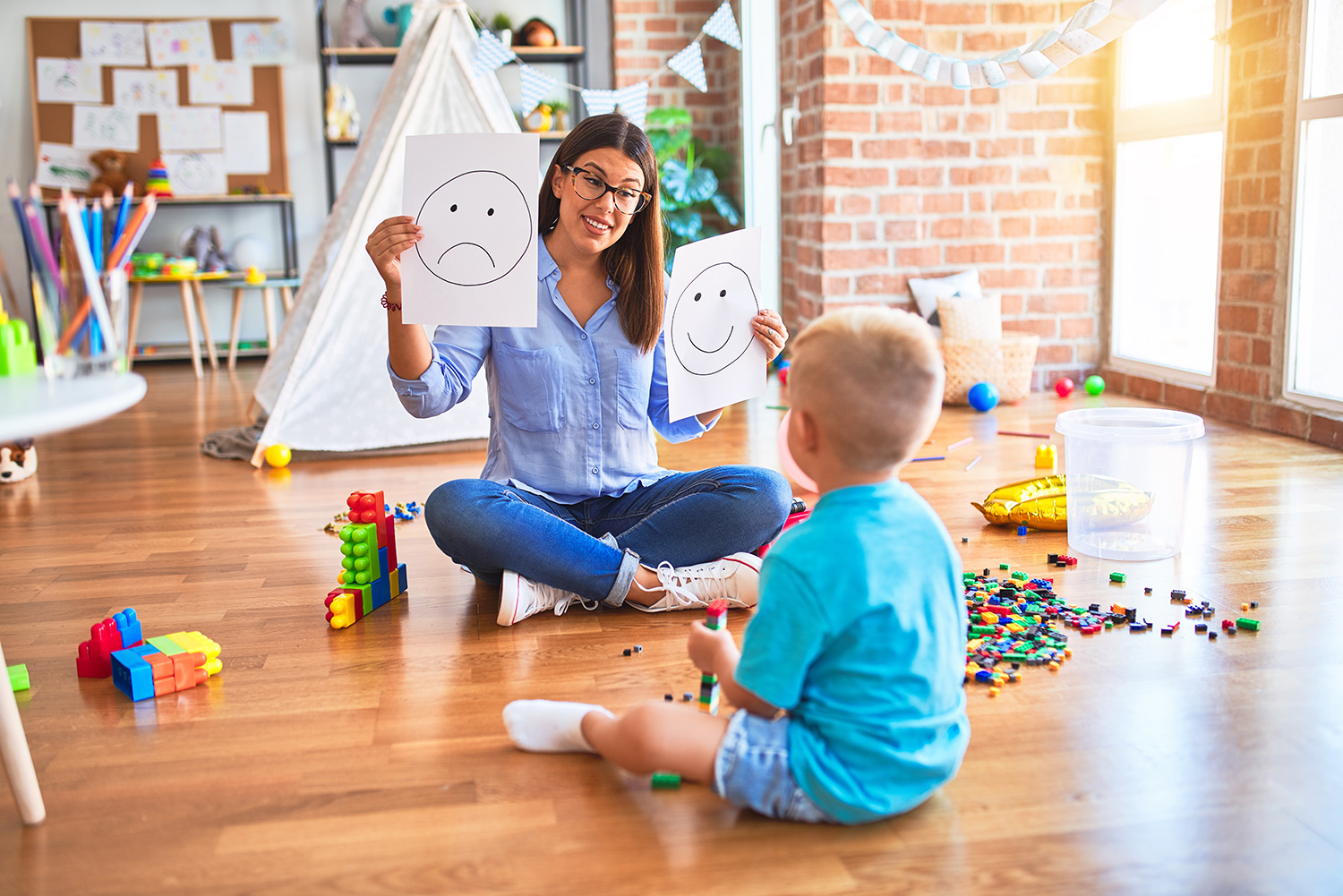 Butterfly Beginnings Counseling with Kim Feeney in Davenport Iowa answers why a Play Therapist can Help-image of therapist playing with child on floor