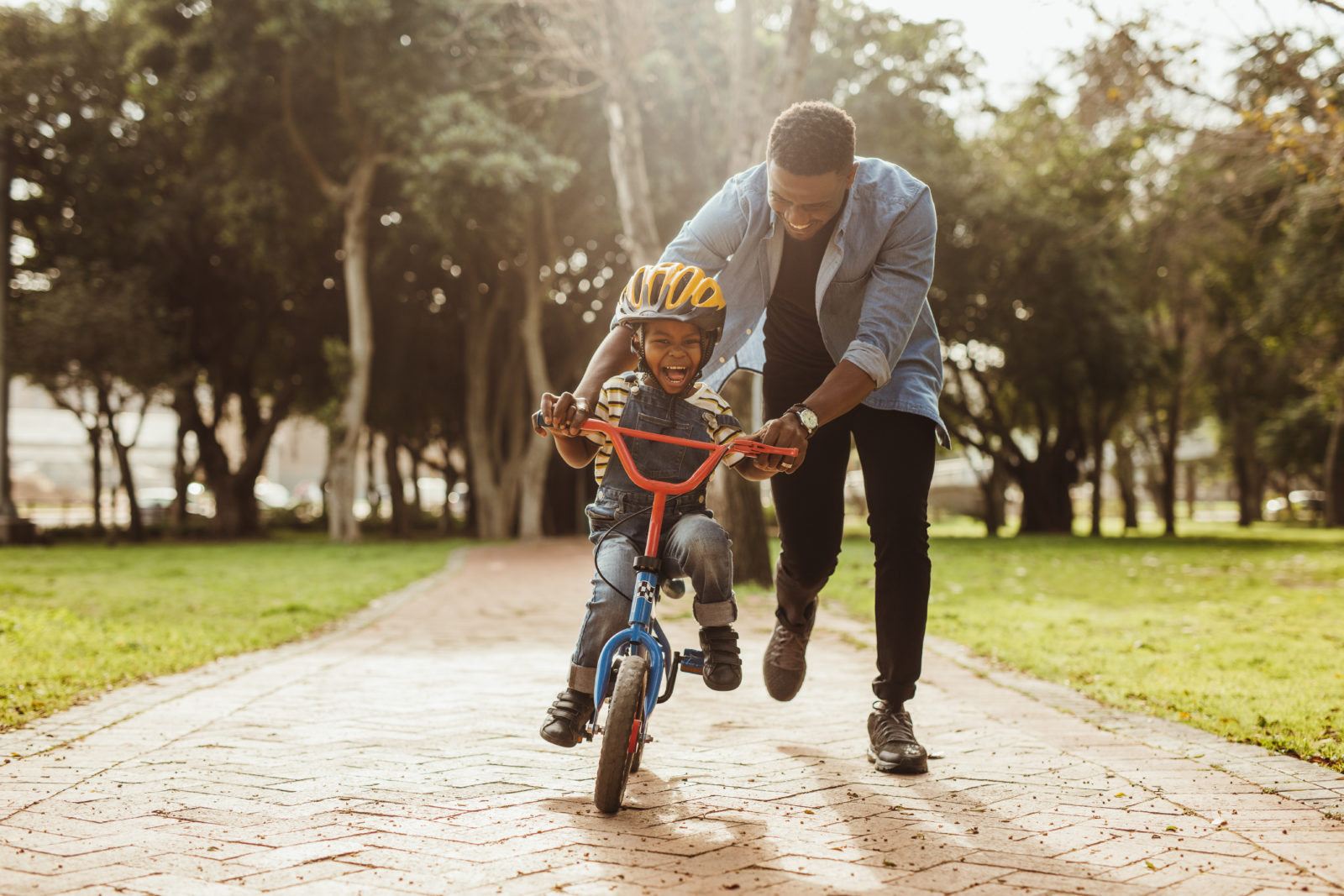 Father Encourages and Praises Son Riding a Bike at Butterfly Beginnings Play Therapy in Davenport, Iowa